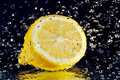 Half of lemon with stopped motion water drops Royalty Free Stock Images