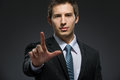 Half length portrait of business man forefinger gesturing who wears suit and black tie Stock Photography