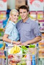 Half length portrait of couple in the supermarket with cart full food concept consumerism and healthy food Royalty Free Stock Photography