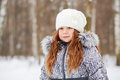 Half length portrait of girl dressed in jacket with fur collar and white knitted hat standing winter park Stock Photography