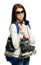 Half length portrait of teenager keeping roller skates handing and wearing sunglasses earphones and rucksack isolated on white Royalty Free Stock Image