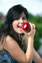 Half length portrait of young woman eating red apple a happy an in background green Royalty Free Stock Photos
