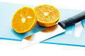 A half of orange fruit and knife in the kitchen Stock Images