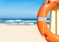 Half orange lifebuoy foreground blue clear sky sea sand background bright sunny day holidays beach beautiful seascape equipment Stock Photos