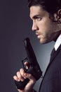 Half portrait of a seductive spy with gun in hand studio shot in low key light Stock Image
