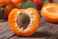 Half ripe apricot closeup on wooden table,  horizontal Royalty Free Stock Photo