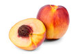 Half a ripe nectarine with a pip juicy its intact resting up against whole fruit on white background Stock Images