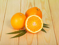 Half and whole orange on the table of light wood Royalty Free Stock Photography