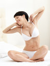 Halfnaked woman stretches herself on the bed Royalty Free Stock Images