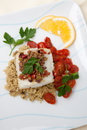 Halibut with olive tapenade crust baked garnished couscous fried cherry tomatoes and fresh parsley Stock Image