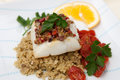Halibut with olive tapenade crust baked garnished couscous fried cherry tomatoes and fresh parsley Royalty Free Stock Image