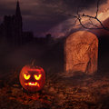 Halloween art design of card concept scary pumpkin on the night cemetery near the tomb focus on pumpkin Stock Image