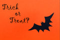 Halloween background with trick or treat an orange a black bat and the words Royalty Free Stock Images