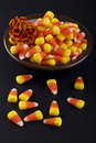 Halloween candies candy corn on the plate flower in black background Stock Image