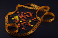 Halloween candies and ribbon on black background Royalty Free Stock Images
