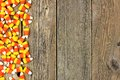 Halloween candy corn side border over old wood