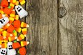 Halloween candy side border against rustic wood Royalty Free Stock Photo
