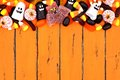 Halloween candy top border over old orange wood