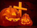 Halloween on cemetery glowing scary gourd and creepy cross flying bats mysterious night autumn seasonal holiday of horror Stock Photo