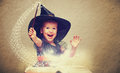 Halloween cheerful little witch with a magic wand and glowing b book conjure laughs Stock Image