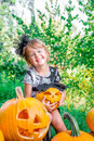 Halloween. Child dressed in black with jack-o-lantern in hand, trick or treat. Happy little girl  pumpkin in the wood, outdoors. Royalty Free Stock Photo