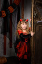 halloween devil girl opening old door Royalty Free Stock Photo