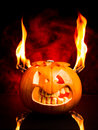 Halloween evil pumpkin with flames and red smoke in the background face of Royalty Free Stock Photos
