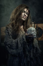 Halloween the evil witch with a skull in his hands middle ages Royalty Free Stock Photo