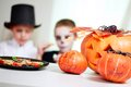 Halloween festive photo of pumpkins and sweets on table with eerie boys on background Royalty Free Stock Photos