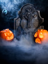 Halloween foggy night with pumpkins tombstone mo angry face and scared face of moon and bat on misty dark background Stock Photos