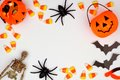 Halloween frame of scattered candy and decor over white Royalty Free Stock Photo