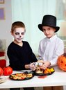 Halloween fright photo of twin boys holding spooky eyes just in skull eye sockets and looking at camera Royalty Free Stock Images