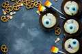 Halloween fun food - eye muffins, cookies, candy corn, marshmallow pops on a stone background top view