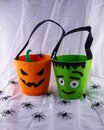Halloween fun for kids going out to trick or treat. Orange Pumpkin and Green monster candy bags in a nest of black spiders Royalty Free Stock Photo