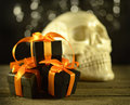 Halloween gifts with skull black and orange gift boxes blurred human behind Stock Image