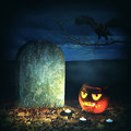 Halloween horror concept scary pumpkin in cemetery jack o lantern with candle light inside the near the grave stone Stock Photos