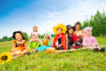 Halloween with kids in costumes sit outside on the grass of field and smile Royalty Free Stock Photo