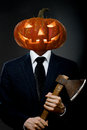Halloween man in black costume with pumpkin head with axe concept Stock Photo