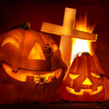 Halloween night closeup on glowing carved pumpkin with creepy spiders and cross on graveyard burning fire in the hell party Royalty Free Stock Photography