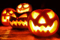 Halloween night group of spooky jack o lanterns lit at Royalty Free Stock Photos