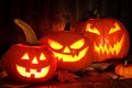 Halloween night scene with spooky Jack o Lanterns against wood