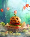 Picture : Halloween party burger in shape of scary pumpkin   on natural wooden board. Halloween food concept  about