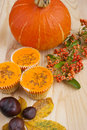 Halloween party cakes autumn arrangement of orange pumpkin pyracanthas berries and cup with chocolate sprinkles on a wooden table Royalty Free Stock Photo