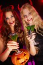 Halloween party photo of smiling females holding pumpkin and cocktails with scorpions Royalty Free Stock Photos