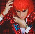 Halloween. Portrait of a beautiful girl in a red wig with horns closeup. Red, festive makeup. Royalty Free Stock Photo