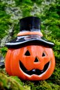 Halloween pumpkin ceramic figurine with a face on the moss Stock Photos