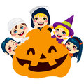 Halloween pumpkin children five cute in scary monster costumes holding a big face Royalty Free Stock Image