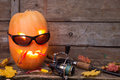 Halloween pumpkin in eyeglass with fishing tackles head on wooden boards background Stock Image