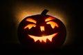 Halloween pumpkin head jack lantern with burning candles on orange background