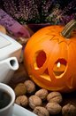 Halloween pumpkin walnuts and coffee still life of carved pot cup of hot black Royalty Free Stock Photo